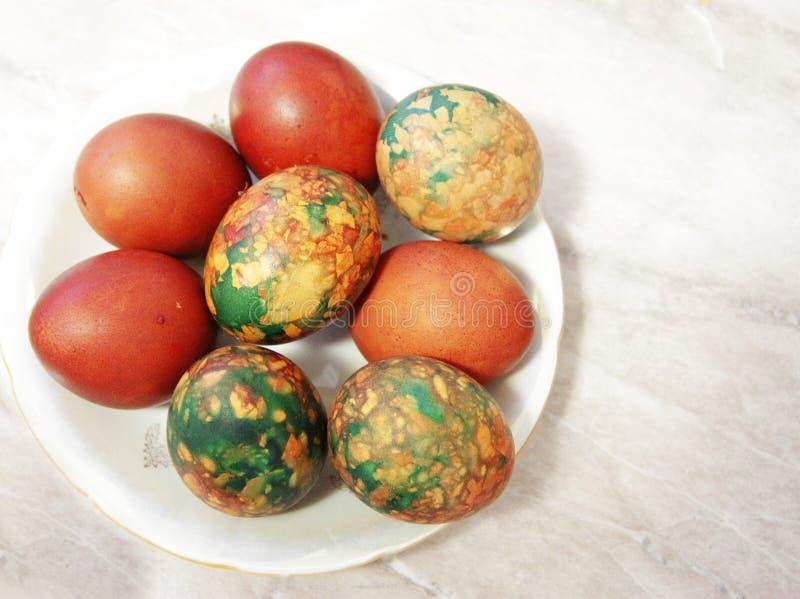 在堆安置的白色板材的五颜六色的复活节彩蛋 免版税库存图片