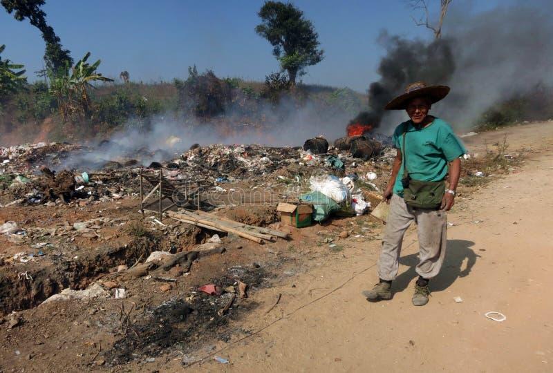 在堆的一个微笑的缅甸人身分灼烧的垃圾前面 库存照片