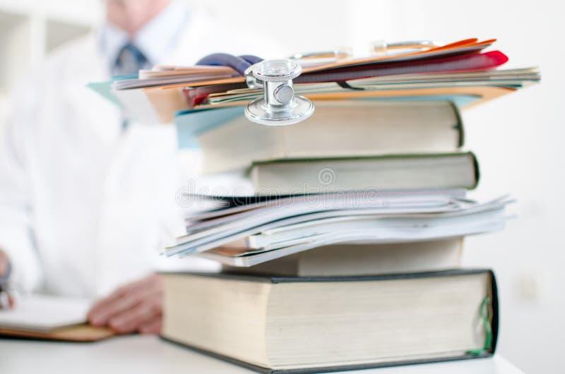 在堆的听诊器医疗书 免版税库存照片