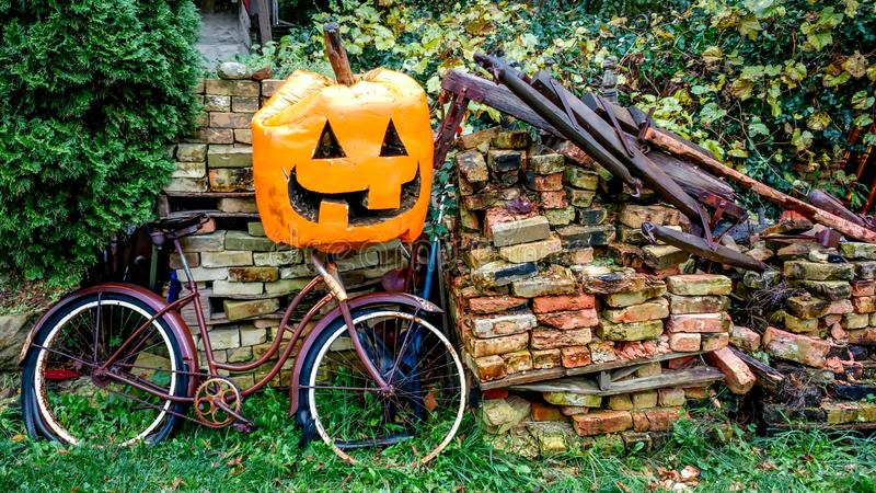 在堆的大南瓜与老自行车的砖 库存照片