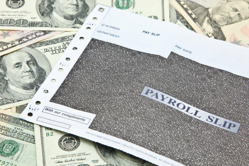 在堆的工资单滑动美元钞票 免版税库存图片