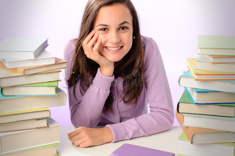 在堆的微笑的学生女孩书之间 免版税库存图片