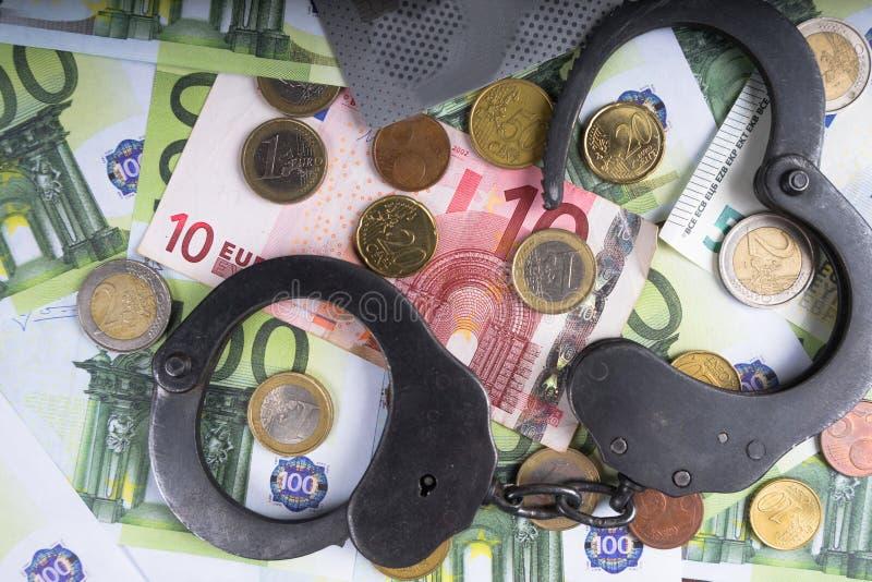 在堆的手铐欧洲钞票 经济罪行的象征意义 图库摄影