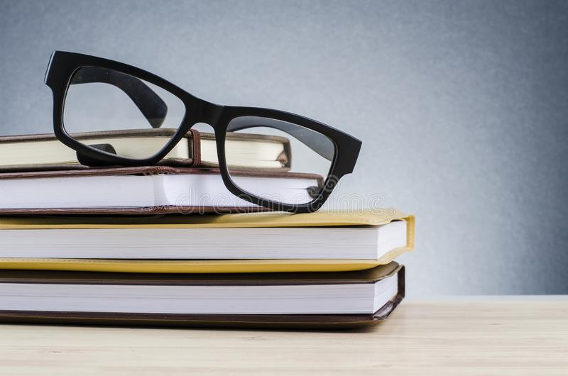 在堆的眼镜在美好的梯度背景的书与回荡 库存照片