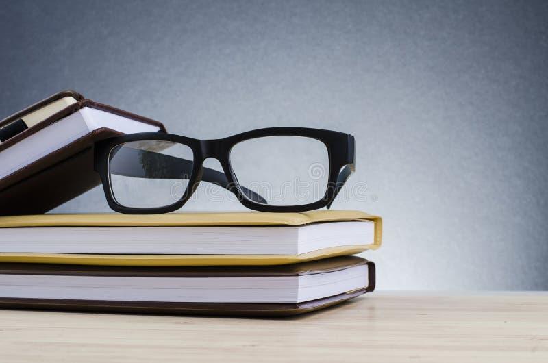 在堆的眼镜在美好的梯度背景的书与回荡 免版税库存图片