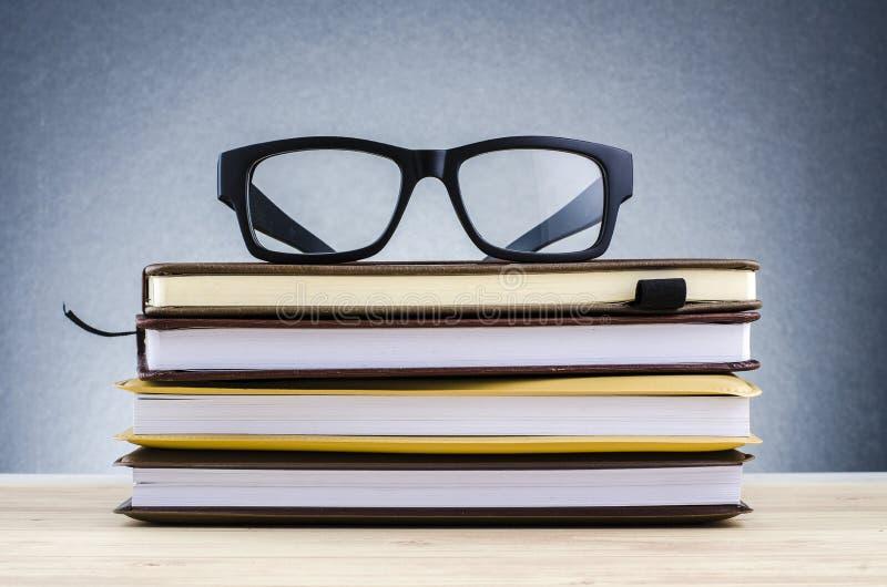 在堆的眼镜在美好的梯度背景的书与回荡 库存图片
