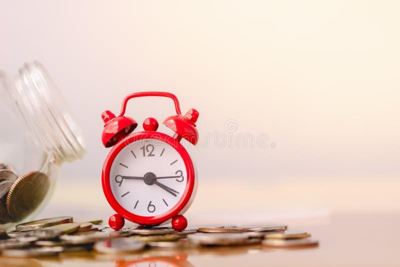 在堆的红色闹钟在储款和金钱生长或者能量救球的概念的硬币 r 免版税库存照片