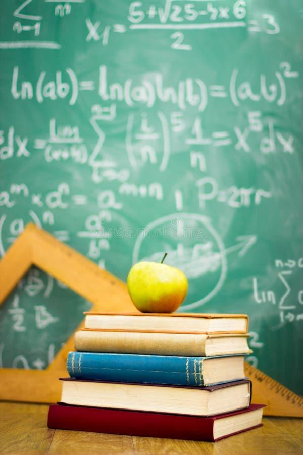 在堆的苹果计算机与黑板的书 免版税图库摄影