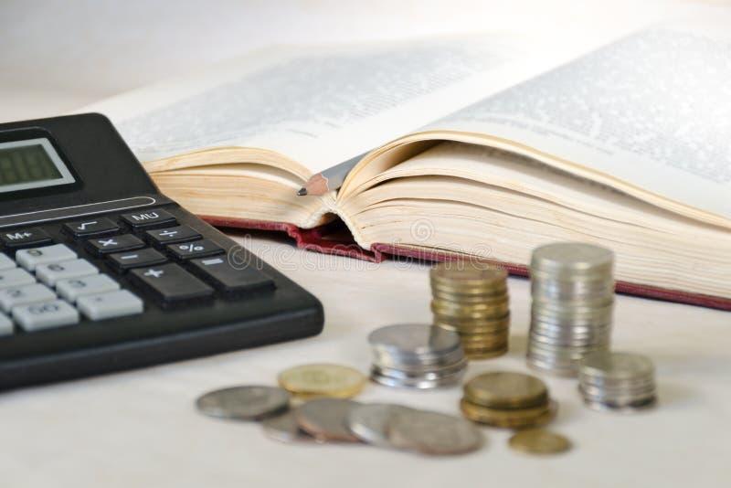 在堆的被弄脏的反对一本开放书的背景的硬币和计算器 高等教育费用的概念 免版税库存照片