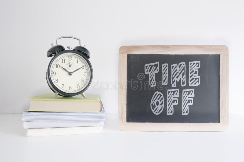 在堆的闹钟在一个黑板旁边的书有文本时间的描写把描写对此 空的拷贝空间 免版税库存照片