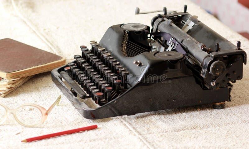 在堆老笔记本,对镜片和一支铅笔旁边的黑葡萄酒金属类型作家在一张亚麻制桌布 库存照片