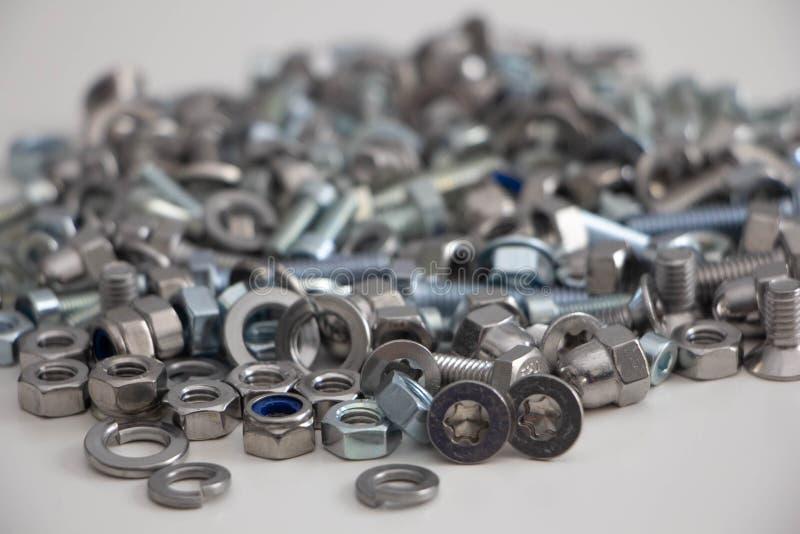 在堆,在灰色背景的正面图的各种各样的螺栓、坚果、螺丝和洗衣机堆  免版税库存照片