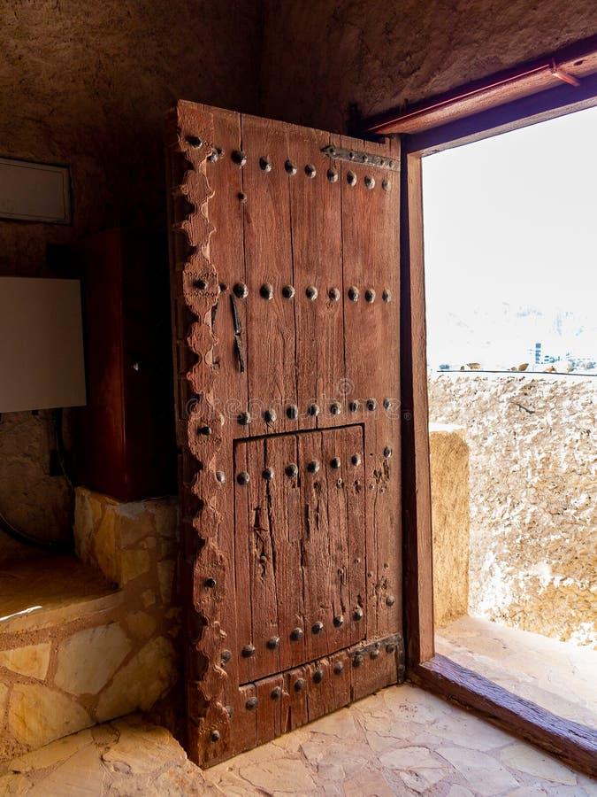 在堡垒马托拉在马斯喀特,阿曼的首都的巨型的古色古香的门 免版税库存照片