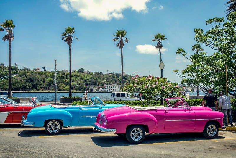 在堤防的减速火箭的明亮的敞蓬车汽车在老哈瓦那 库存照片