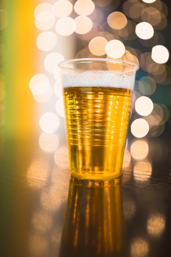 在塑料一次性杯子,欢乐光背景的桶装啤酒 免版税图库摄影