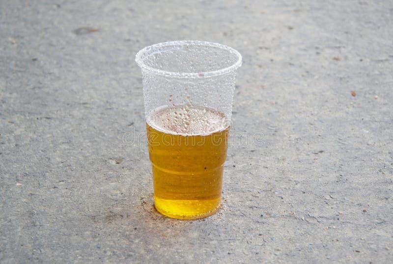 在塑料杯子的黄色饮料啤酒在路面 免版税库存照片