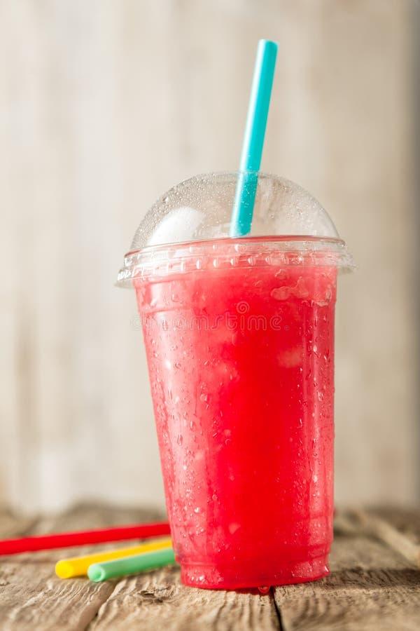 在塑料杯的红色Slushie饮料有秸杆的 库存图片
