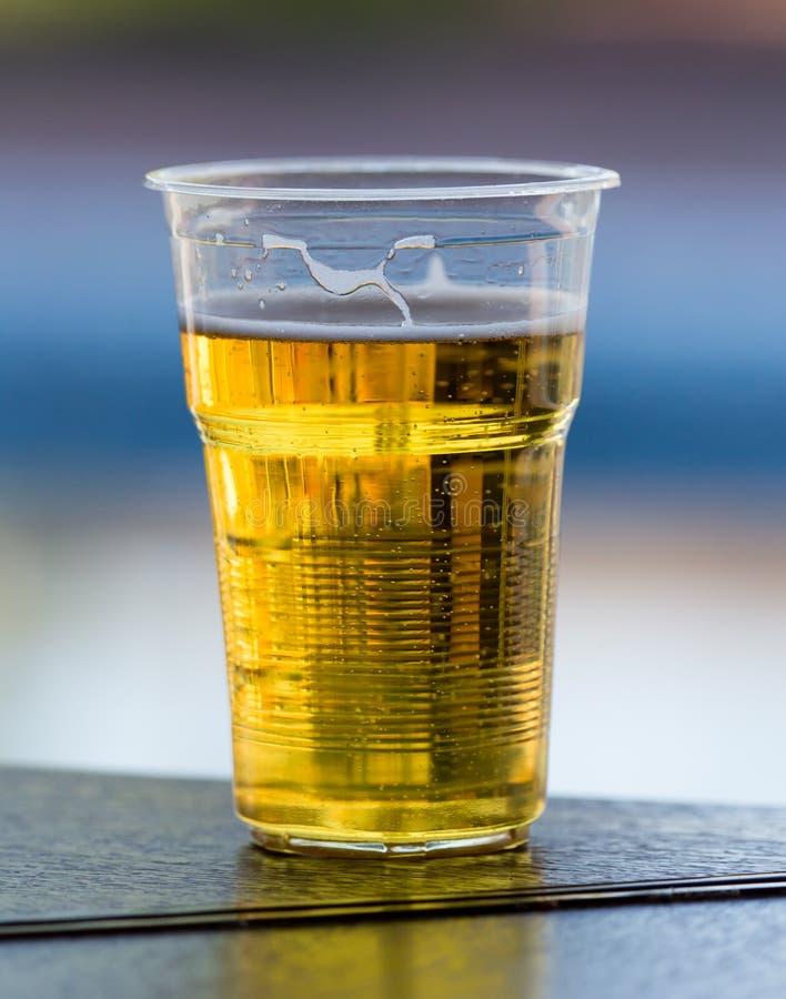 在塑料玻璃的新鲜的啤酒在桌上 免版税库存照片