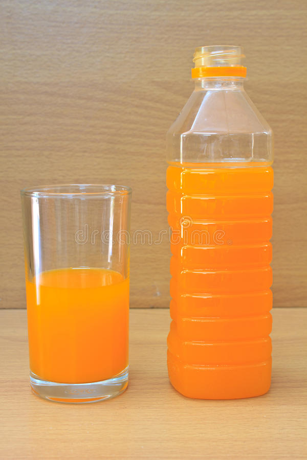 在塑料瓶和玻璃的橙汁 免版税库存照片