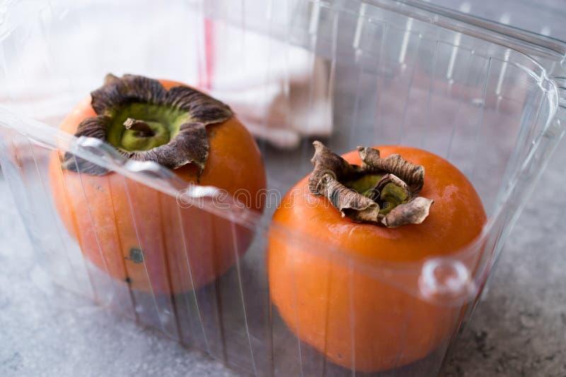 在塑料盒的新鲜的柿子果子 库存图片