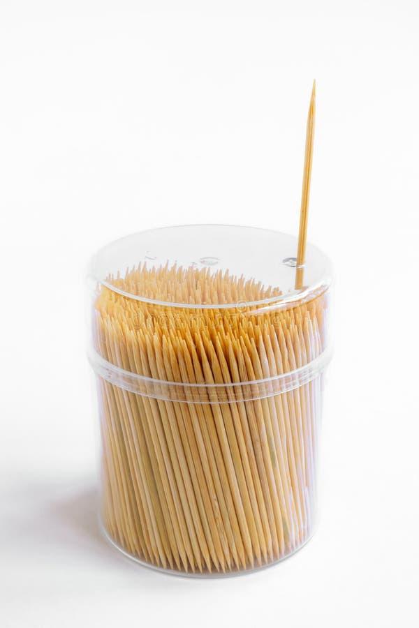 在塑料盒的竹牙签有在白色背景,去掉的一根牙签的盒盖的 库存照片