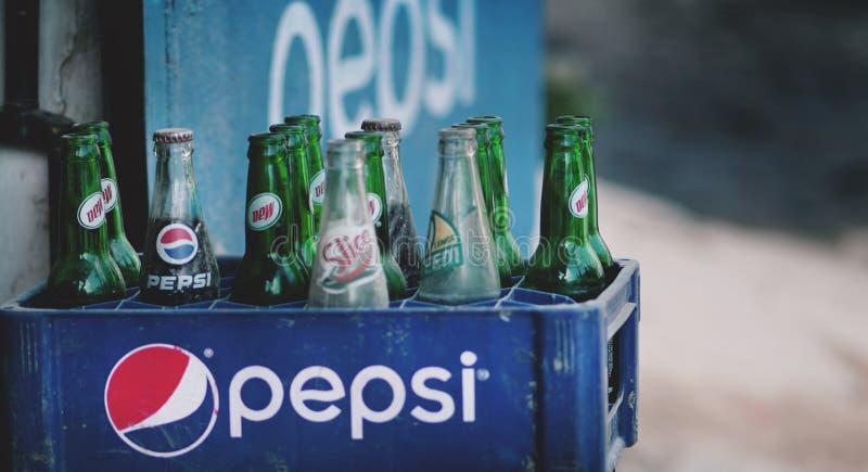 在塑料筐的老多灰尘的百事可乐瓶被卖在Thamel街 免版税库存图片