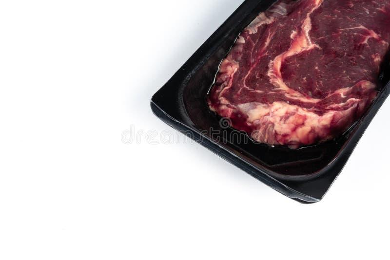 在塑料组装的未加工的牛排 免版税库存照片