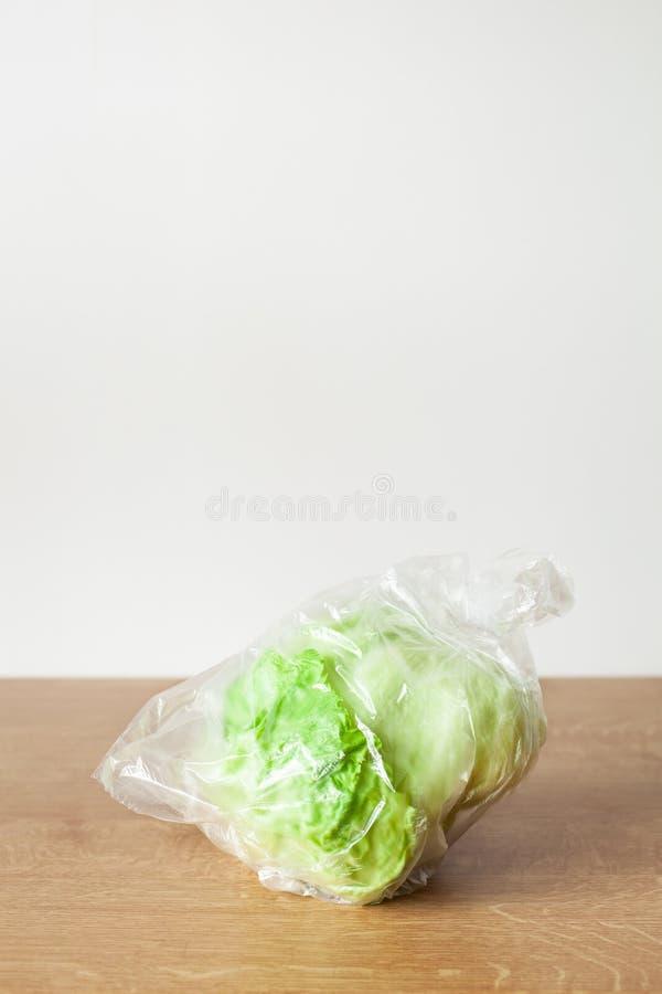 在塑料袋的卷心莴苣菜 单一用途的塑料封装问题 免版税库存照片