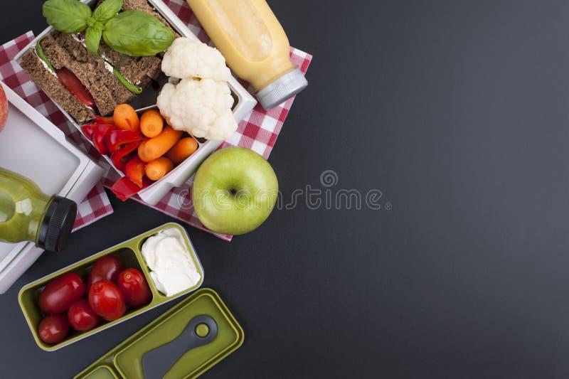 在塑胶容器的学校午餐 从新鲜的莓果和多士的汁液与健康午餐的菜 黑背景和 免版税库存图片