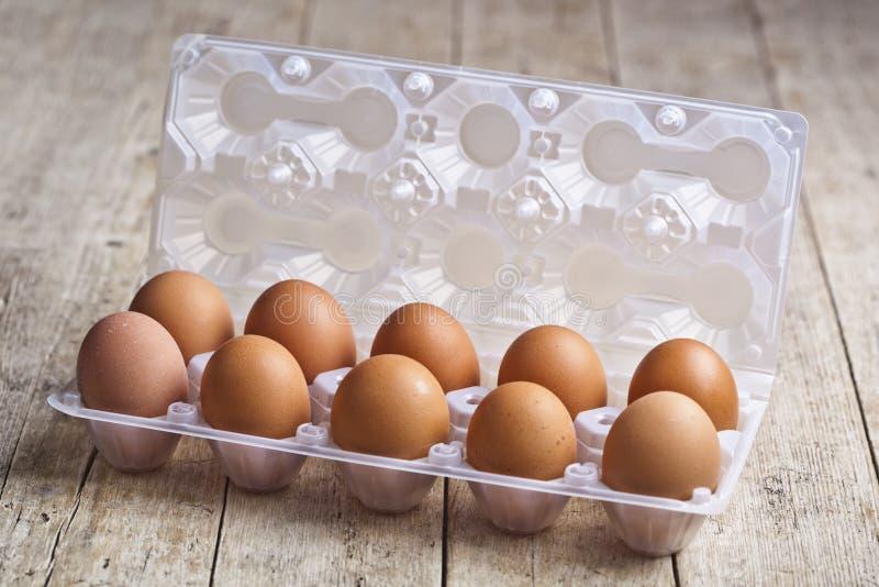 在塑胶容器的新鲜的鸡鸡蛋在土气木桌上 库存照片