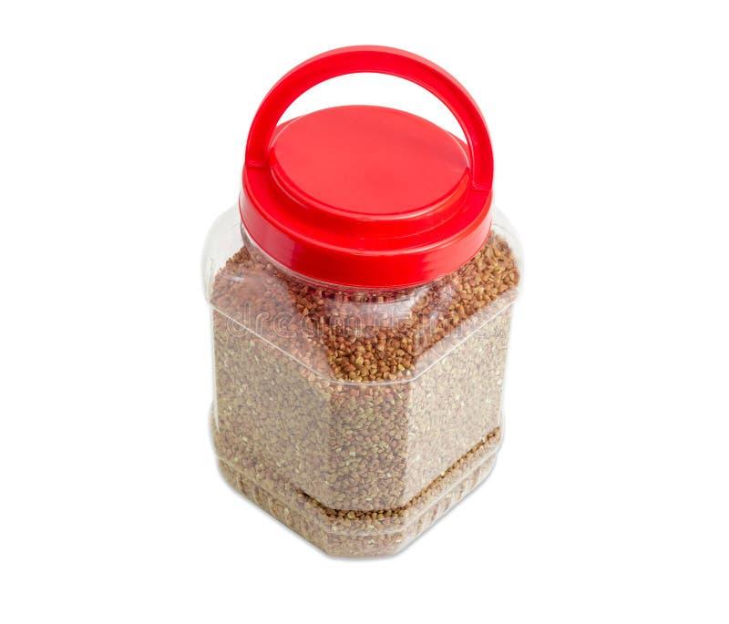 在塑胶容器的碎荞麦片有红色盖子的 免版税图库摄影