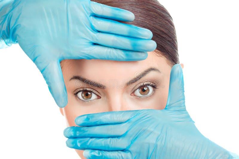 在塑造框架的手套的手在女孩的眼睛附近 免版税库存图片