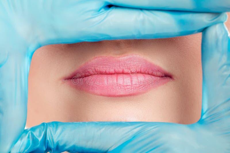 在塑造框架的手套的手在妇女嘴唇附近 库存图片