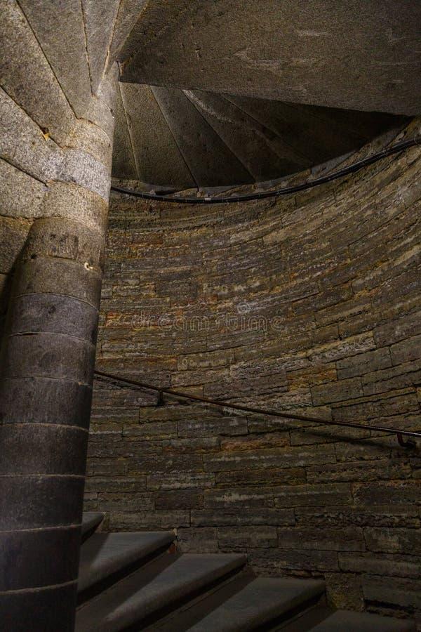 在塔里面的黑暗的石螺旋形楼梯 免版税库存照片