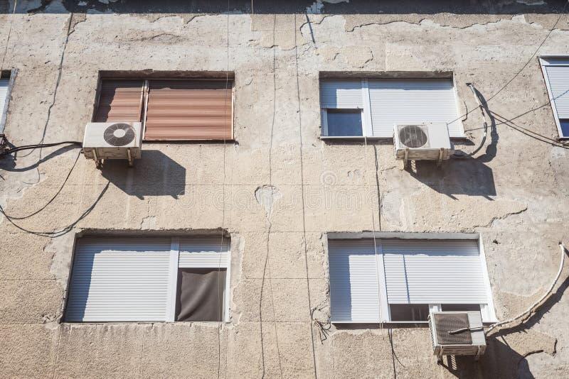 在塞尔维亚、欧洲贝尔格莱德一栋老建筑的破旧立面上,展示着空调设备,或者AC,与粉丝们 库存图片