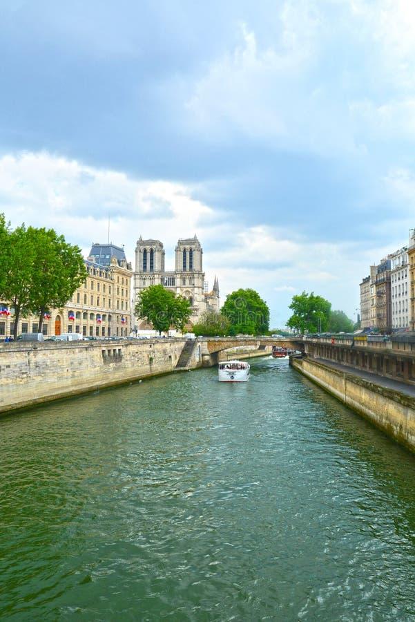 在塞纳河江边和Notre水坝de巴黎的亦称旅游巡航小船我们的巴黎的夫人 库存照片