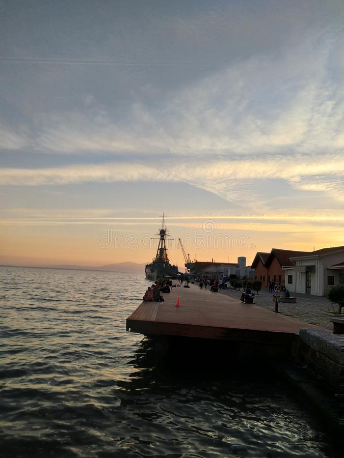 在塞萨罗尼基希腊,惊人的日落港口的老战争驱逐舰船  免版税图库摄影