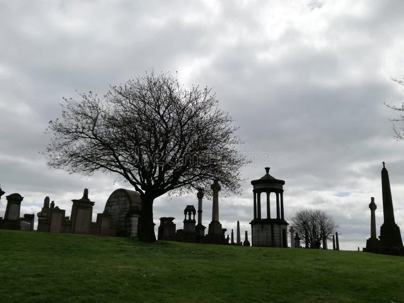在墓碑和树之间的公墓风景在日落期间 库存图片
