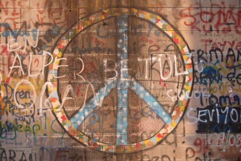 在墙壁上和街道画浪花绘的和平标志 免版税图库摄影