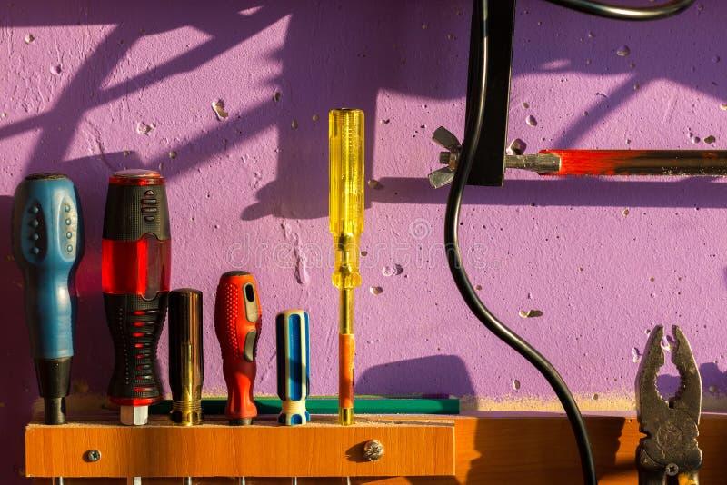在墙壁上固定的一套工具 例如:各种各样的螺丝刀、钳子、金属锯和铅笔 免版税库存图片