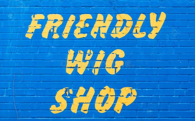 在墙壁上的一个友好的假发商店标志 免版税库存图片