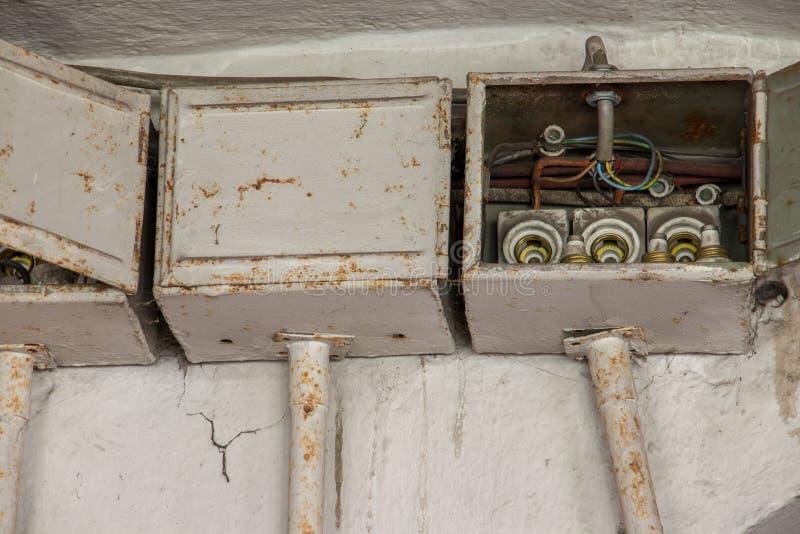 在墙壁上的三个老电子箱子 库存图片