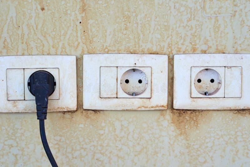 在墙壁上的三个老damger插口有绳子缆绳的接通一个插口 免版税库存照片