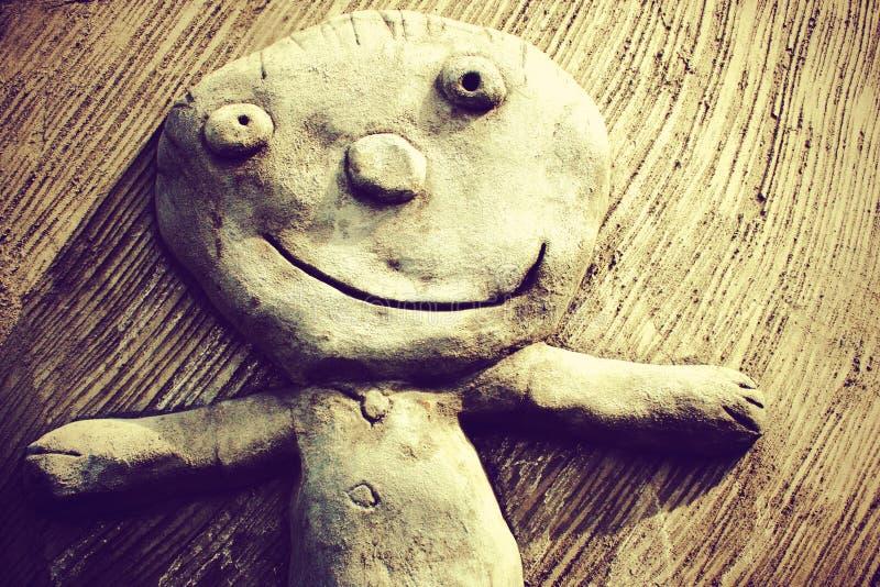 在墙壁上的微笑的儿童雕塑 库存图片