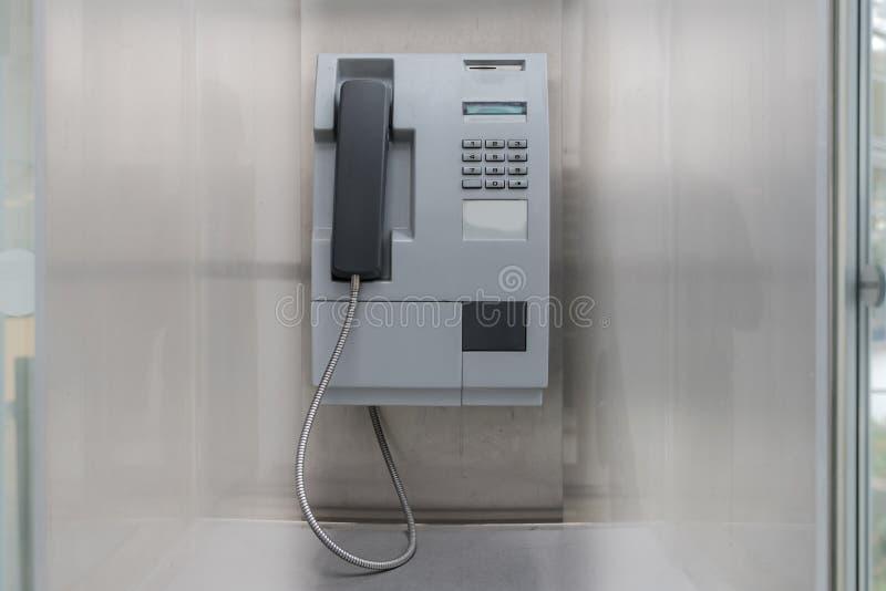 在墙壁上的投入硬币后自动操作的公用电话 免版税库存图片