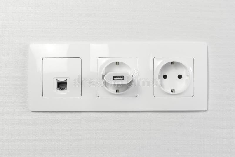 在墙壁上的电子插口有黑连接互联网插座和白色导线的 从充电的设备的适配器有usb输入的 库存图片