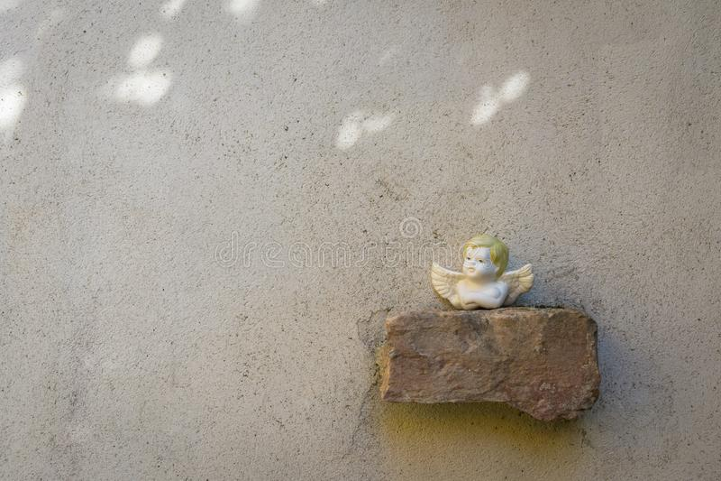 在墙壁上的砖安置的小天使雕塑 图库摄影