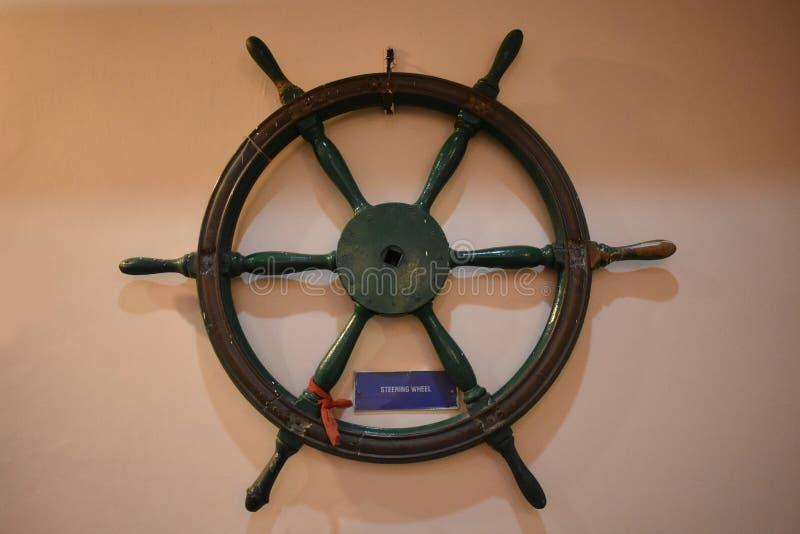 在墙壁上的老木船方向盘船舵 库存图片