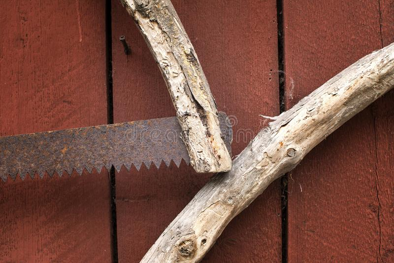 在墙壁上的老生锈的手工制造手锯 免版税库存图片