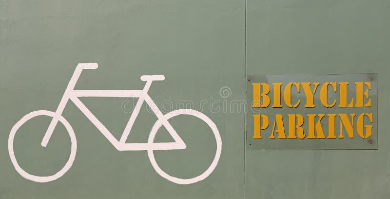 在墙壁上的自行车停放的标志 图库摄影